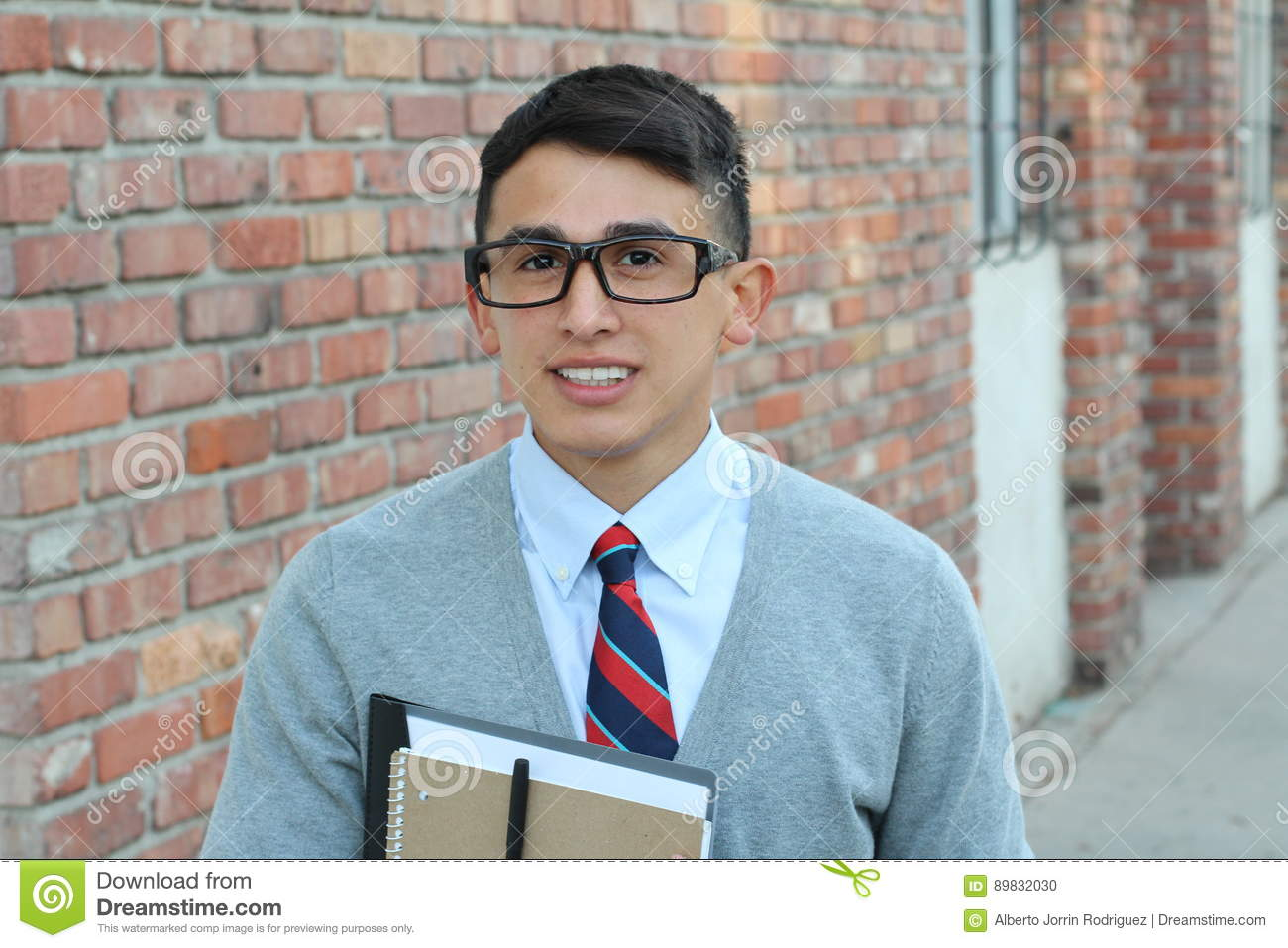 Cute teenager boy in formal high school uniform and glasses smiling