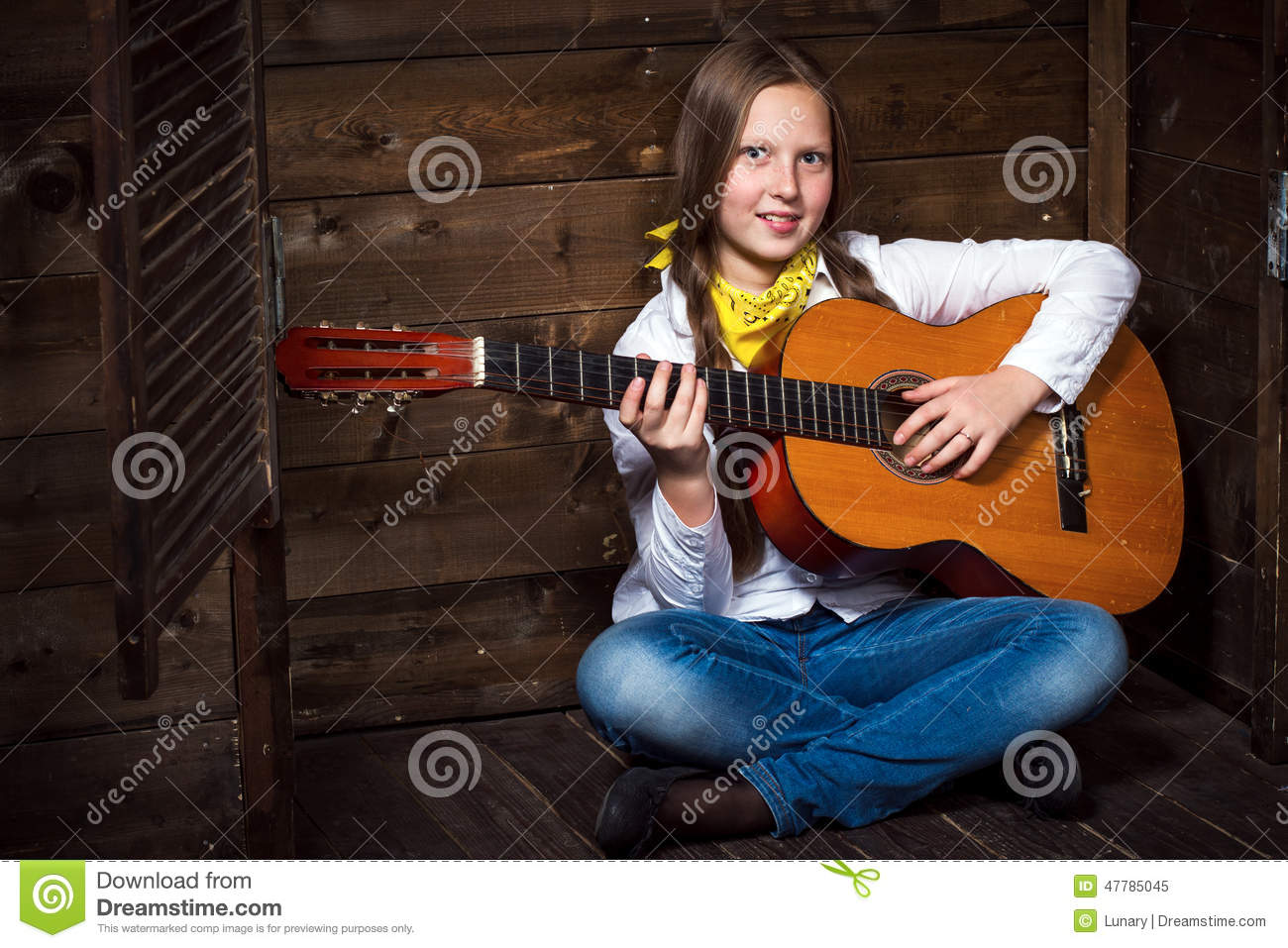 Cute teenager cowgirl plays the guitar