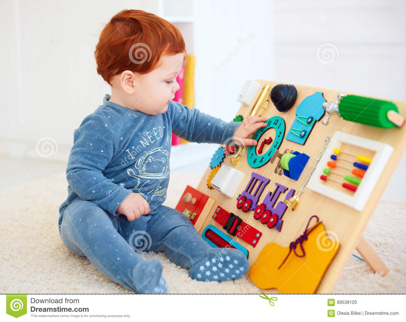 Cute Toddler Baby Playing With Busy Board At Home Stock Photo