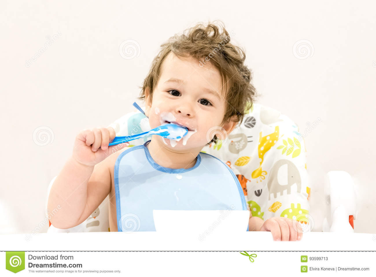 Cute toddler boy with blue spoon is yogurt. the child smiles. funny kid in a baby seat. beautiful 2 year old little boy eating Bre