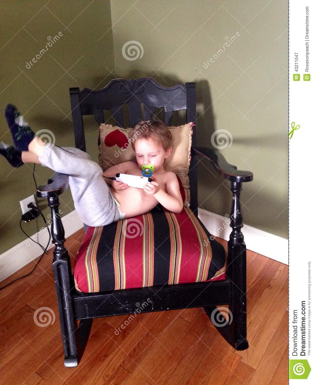 Cute Toddler Boy With A Pacifier And A Cell Phone Stock