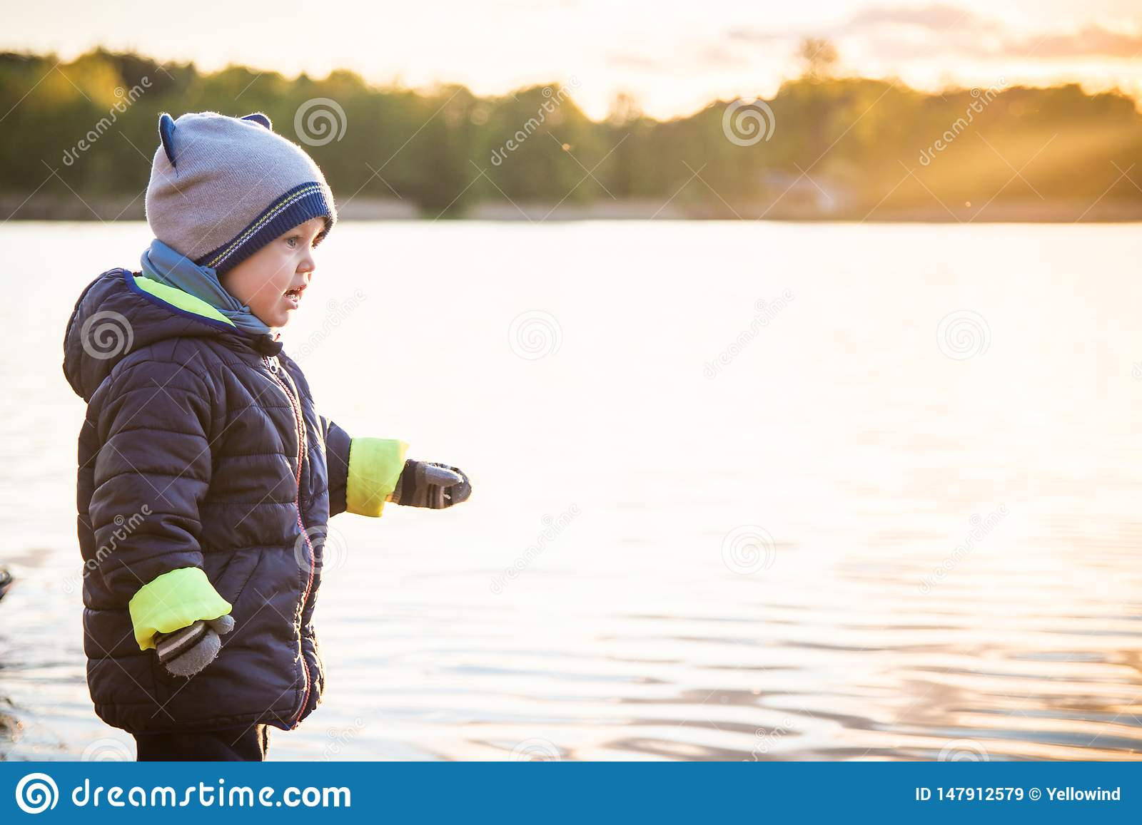 Cute toddler boy in spring clothes near water