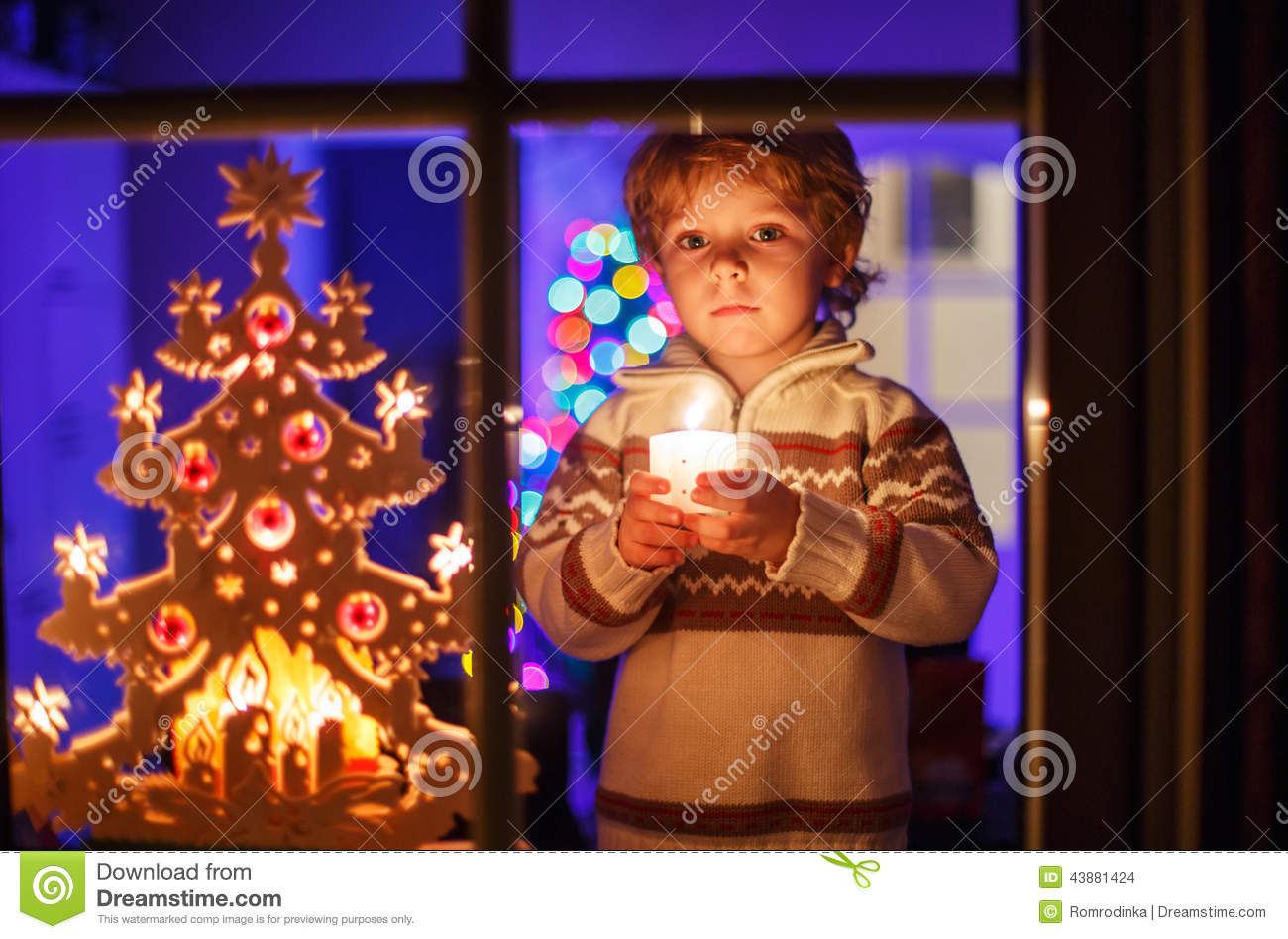 Cute Toddler Boy Standing By Window At Christmas Time And