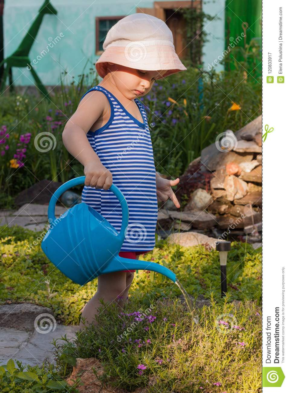 Cute toddler boy in straw hat watering plants in the garden at summer f84768c8949f