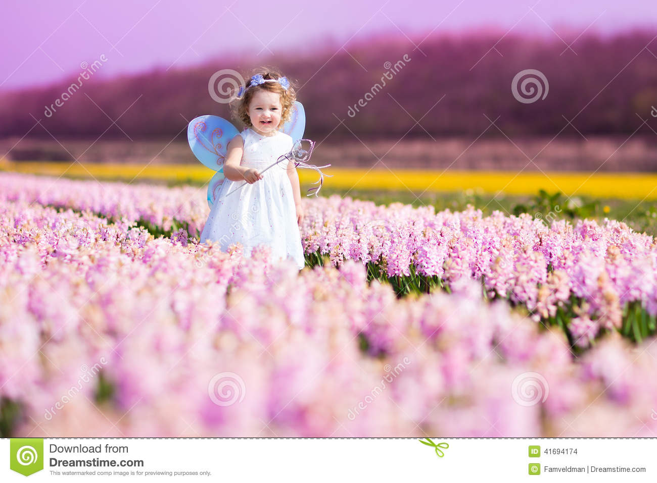 cute toddler girl in fairy costume in a flower field stock