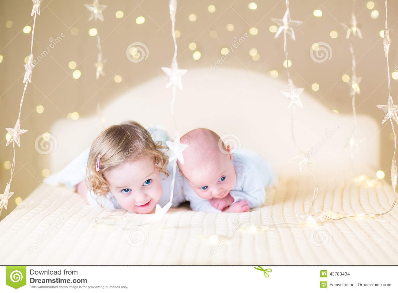 Cute toddler girl and her little newborn baby brother with warm soft lights