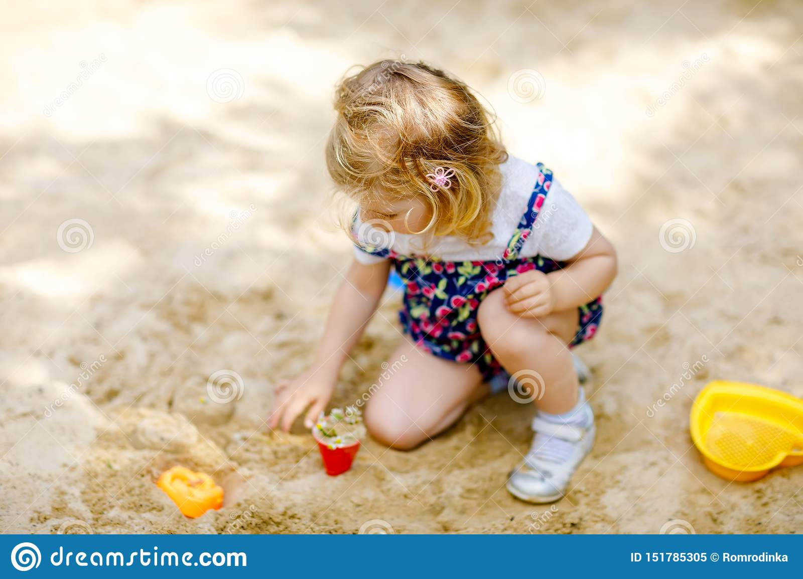 Cute toddler girl playing in sand on outdoor playground. Beautiful baby in red trousers having fun on sunny warm summer