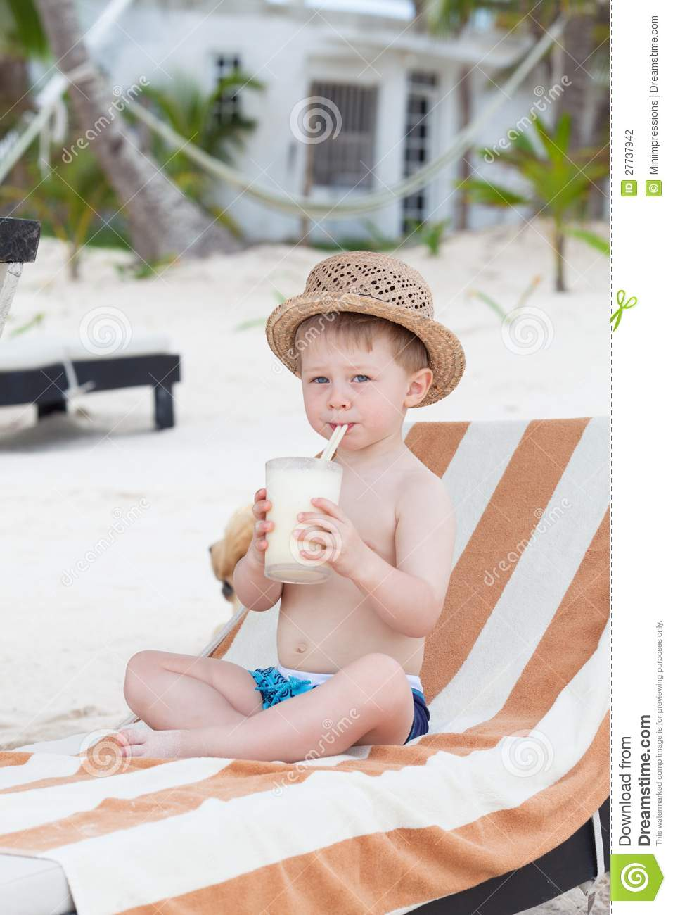Cute toddler sipping milkshake on the beach
