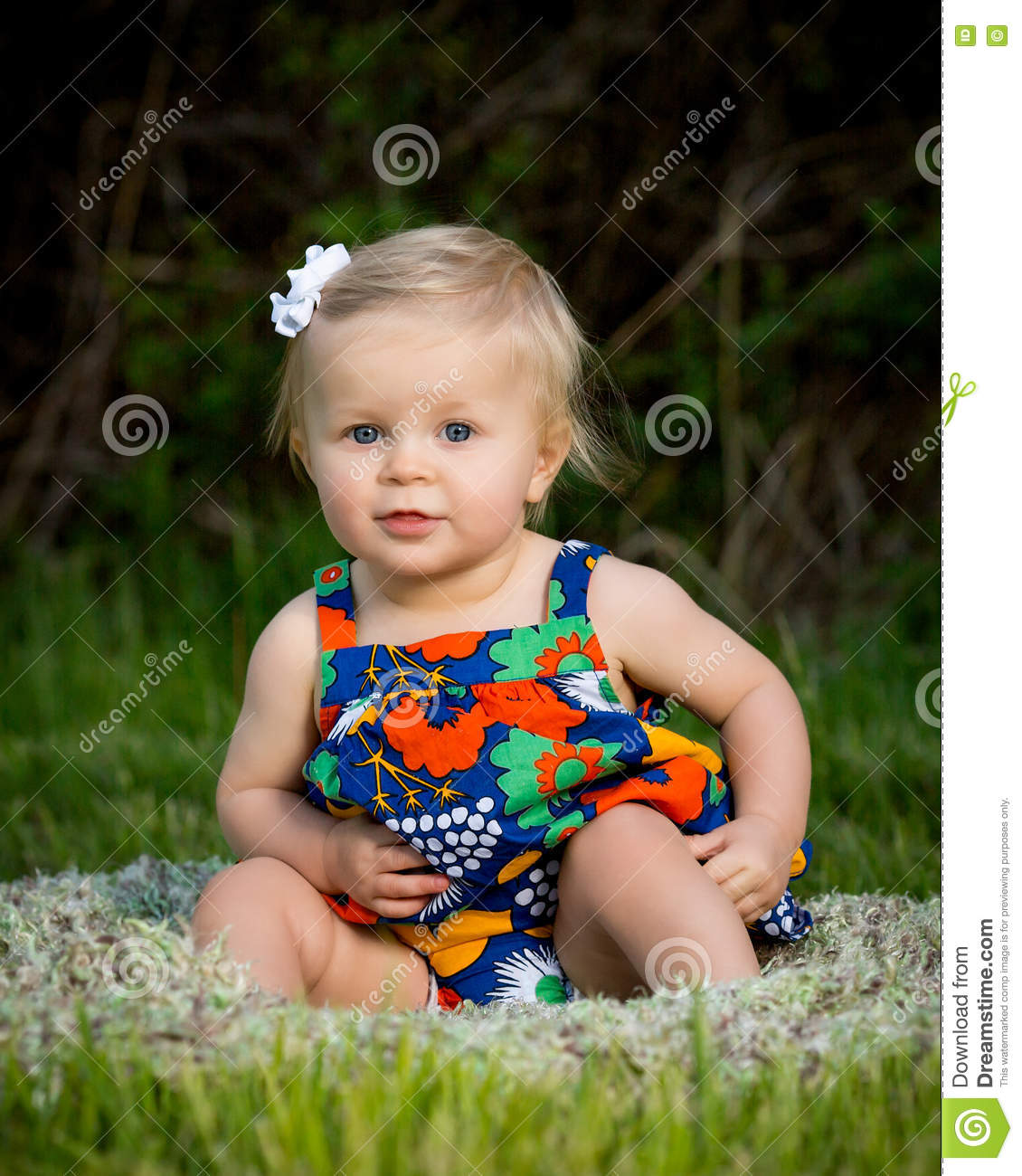 Cute toddler sitting in flowered dress