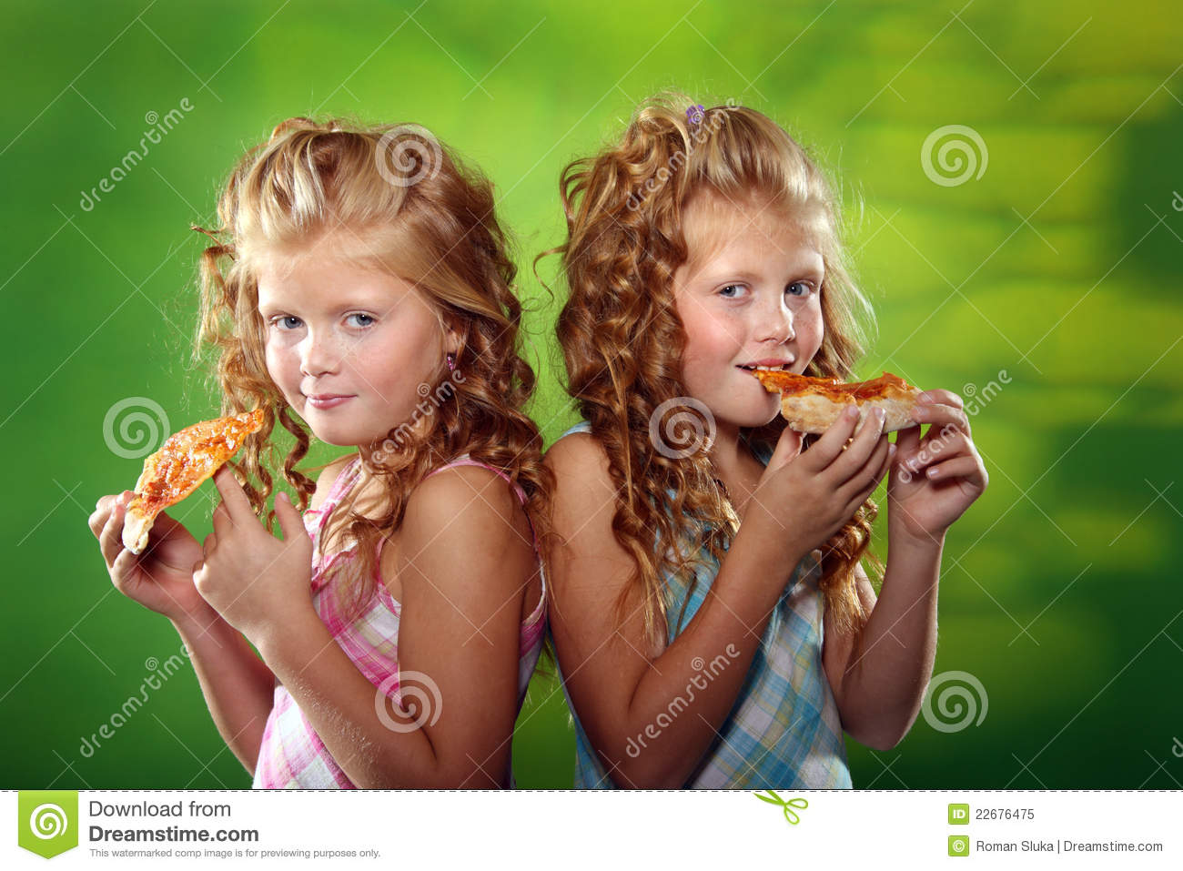 Cute Twin Girls Eating Pizza Royalty Free Stock Photo