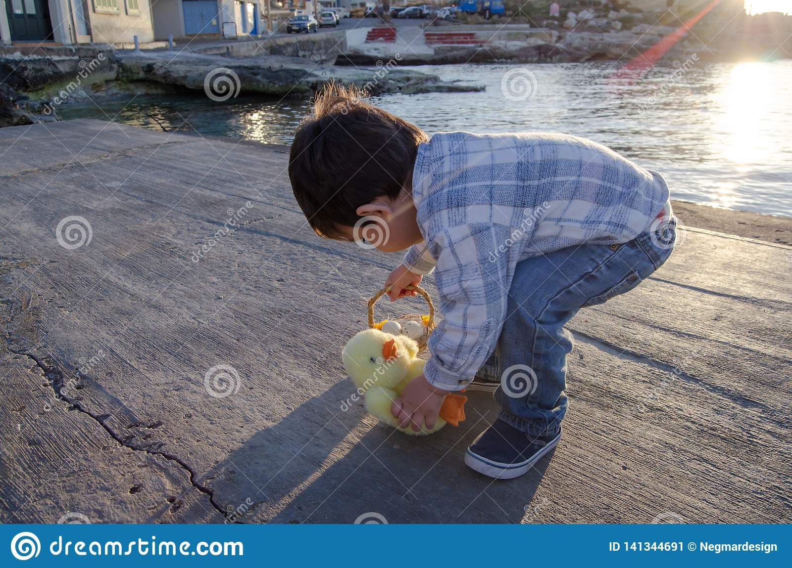 Cute two years old toddler playing with small chicken toy and basket with two easter eggs on the sea doc