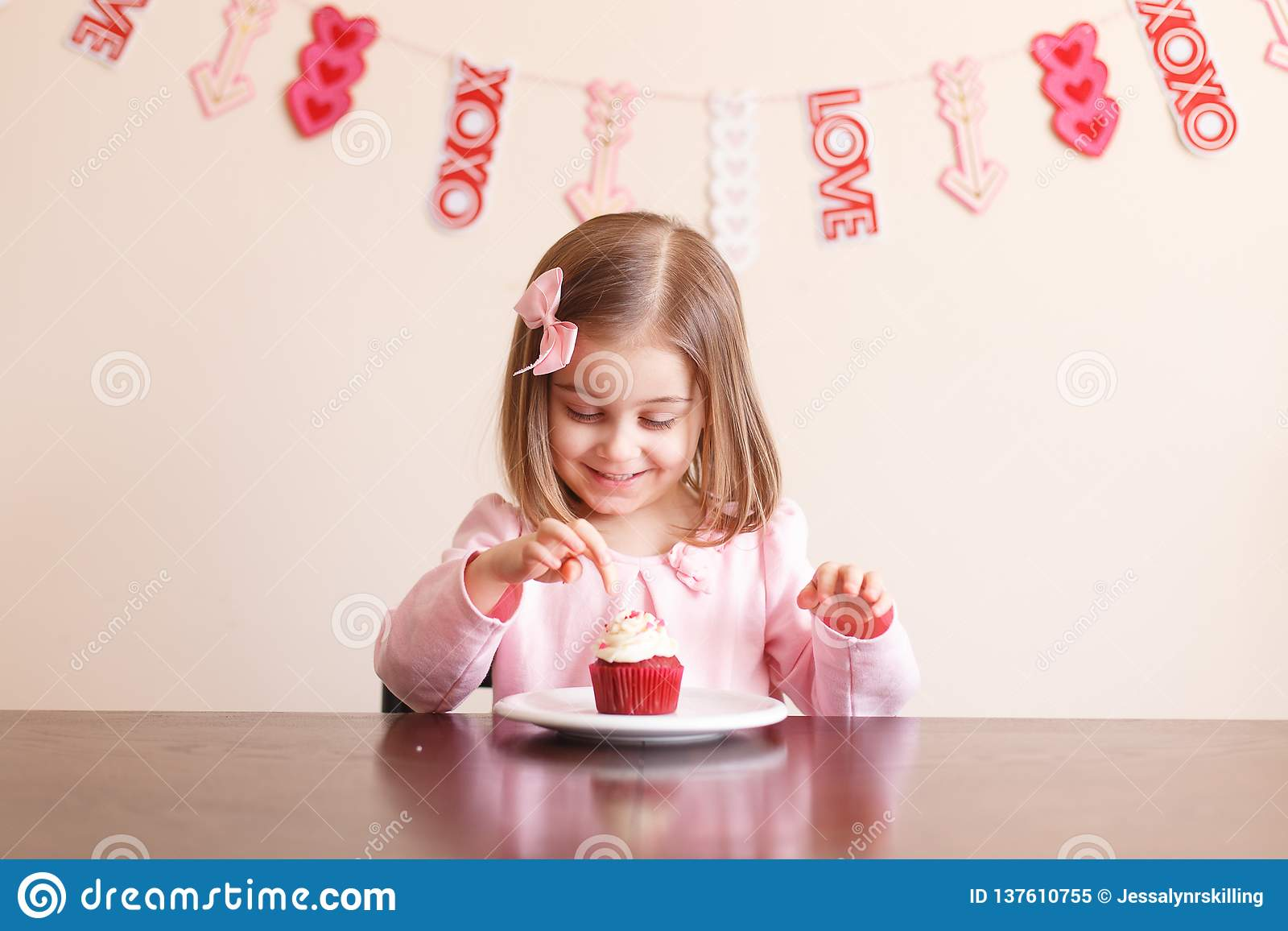 Cute Valentine`s day little girl with cupcake