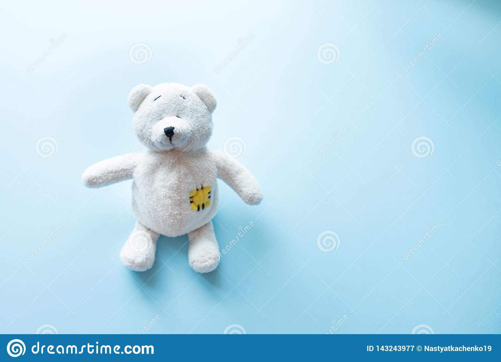Cute white teddy bear child toy with visible upper body and open arms on blue background with copy space
