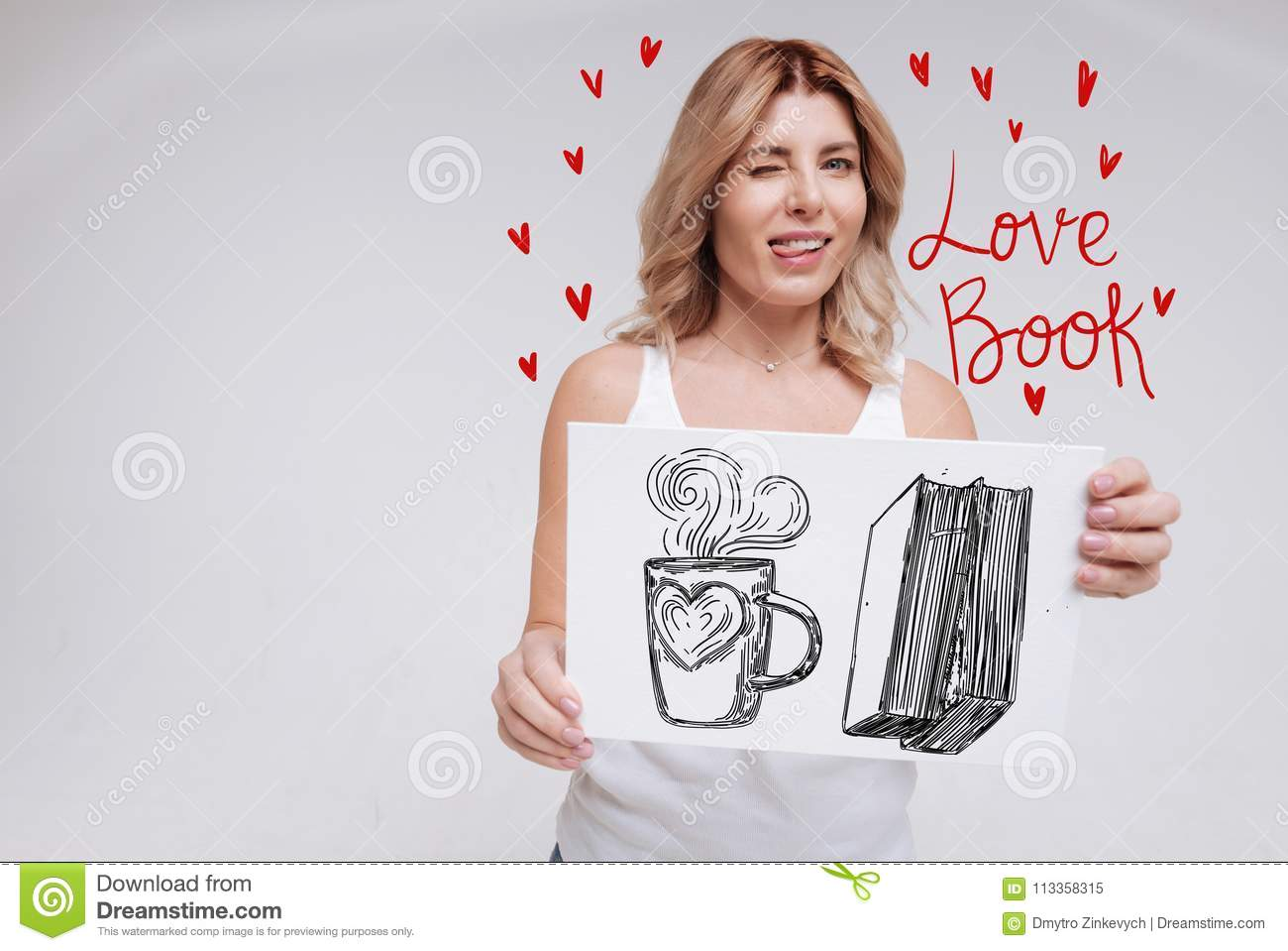 Cute woman biting her tongue while remembering a nice love book