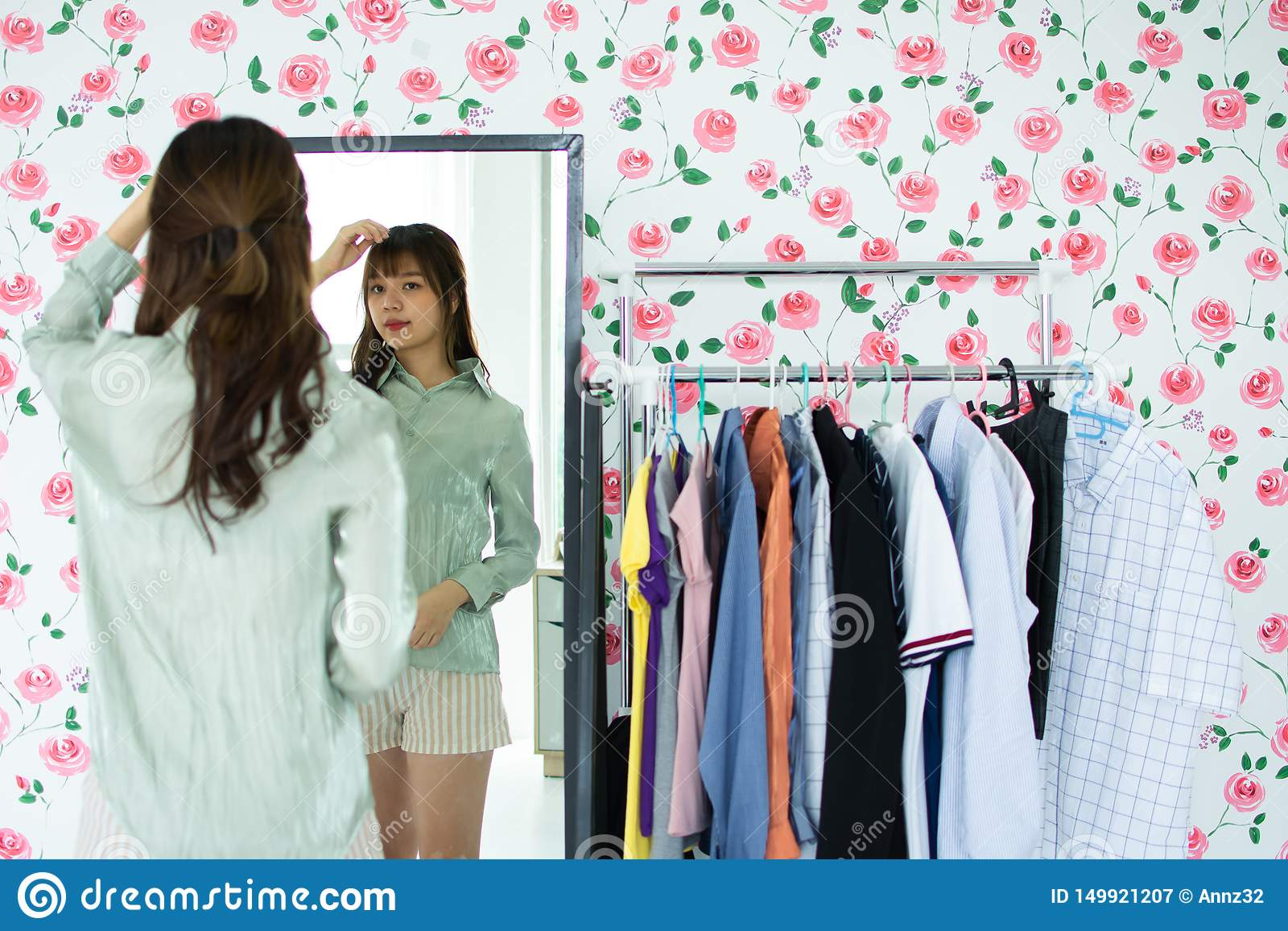 A cute woman is looking at the mirrow in her room