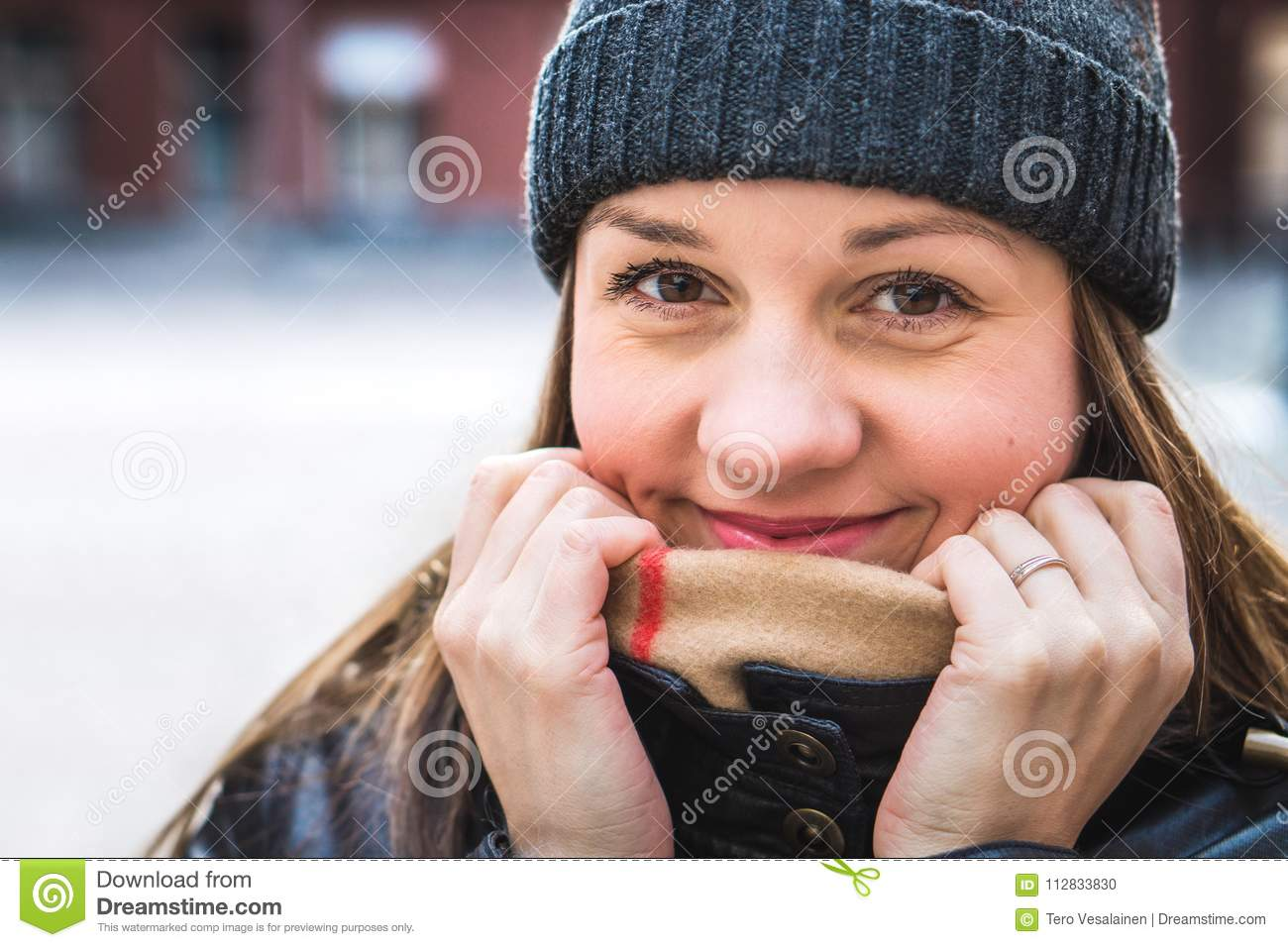 da2303d4ec059 Cute woman wearing a beanie in winter. Happy and smiling person hiding  behind scarf and holding collar with hands. Outdoor lifestyle portrait in  city. Ring ...