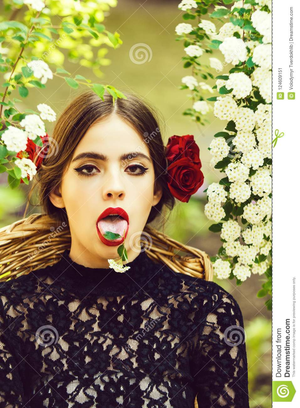 Cute woman with white flower on tongue in open mouth