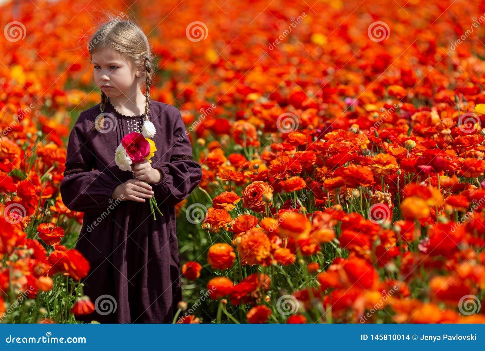 Cute wonderful kid child girl walks in a flowering spring meadow