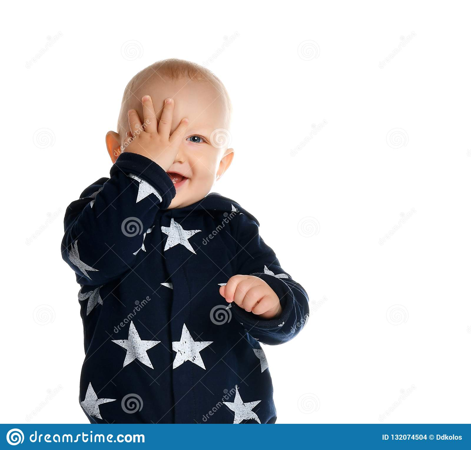 A cute 1 year old stands in a white studio setting.