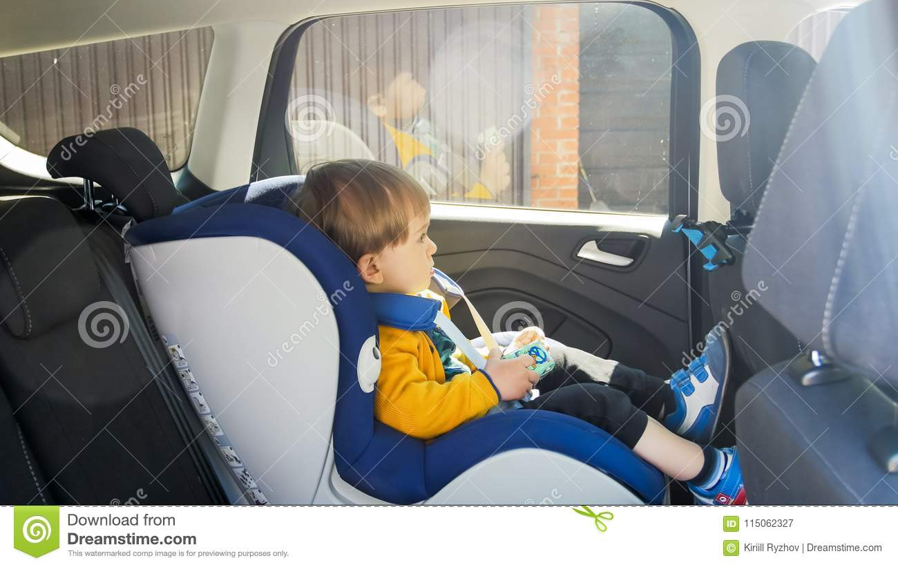 Download Cute 2 Years Old Toddler Boy Sitting With Toy Car In Safety Seat Stock Image