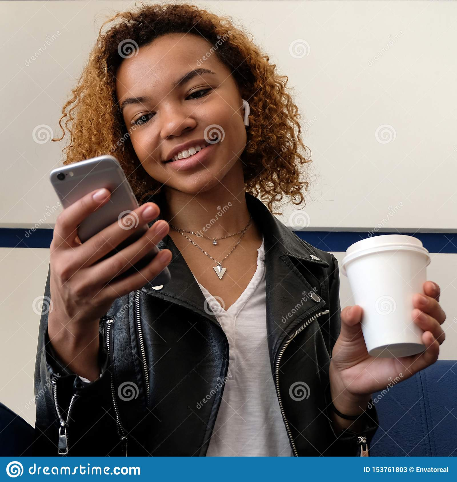 A Cute Young African American Woman Is Holding A Telephone And A Paper Cup Of Coffee Headset Without Wires In The Ear Listening Stock Image Image Of Cellphone Afro 153761803