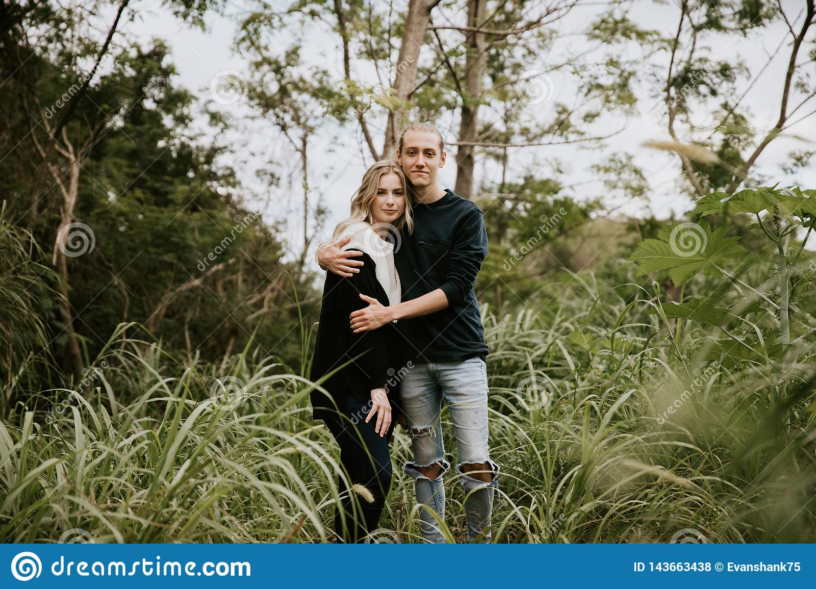 Cute Young Attractive Dating Couple Looking, Smiling, and Laughing in the Dense  Green Tropical Forest Jungle