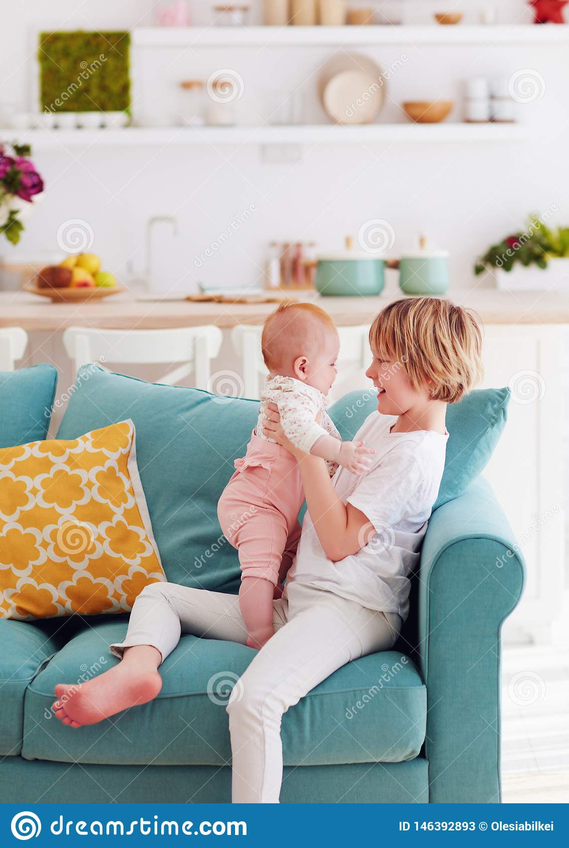 Cute young boy playing with little infant baby sister at home on the couch