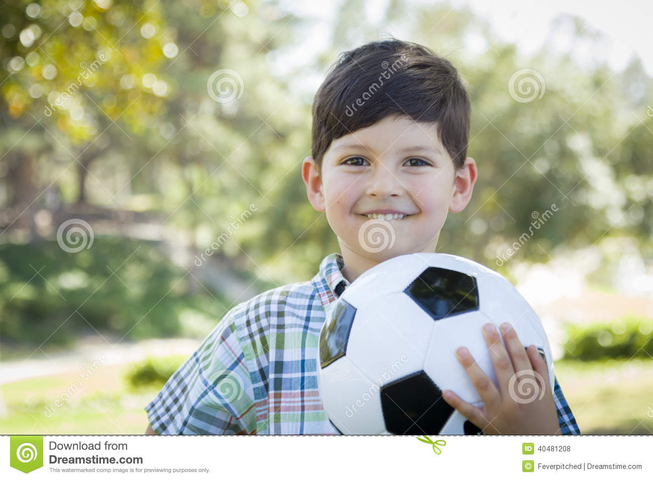 Cute Young Boy Playing With Soccer Ball In Park Stock
