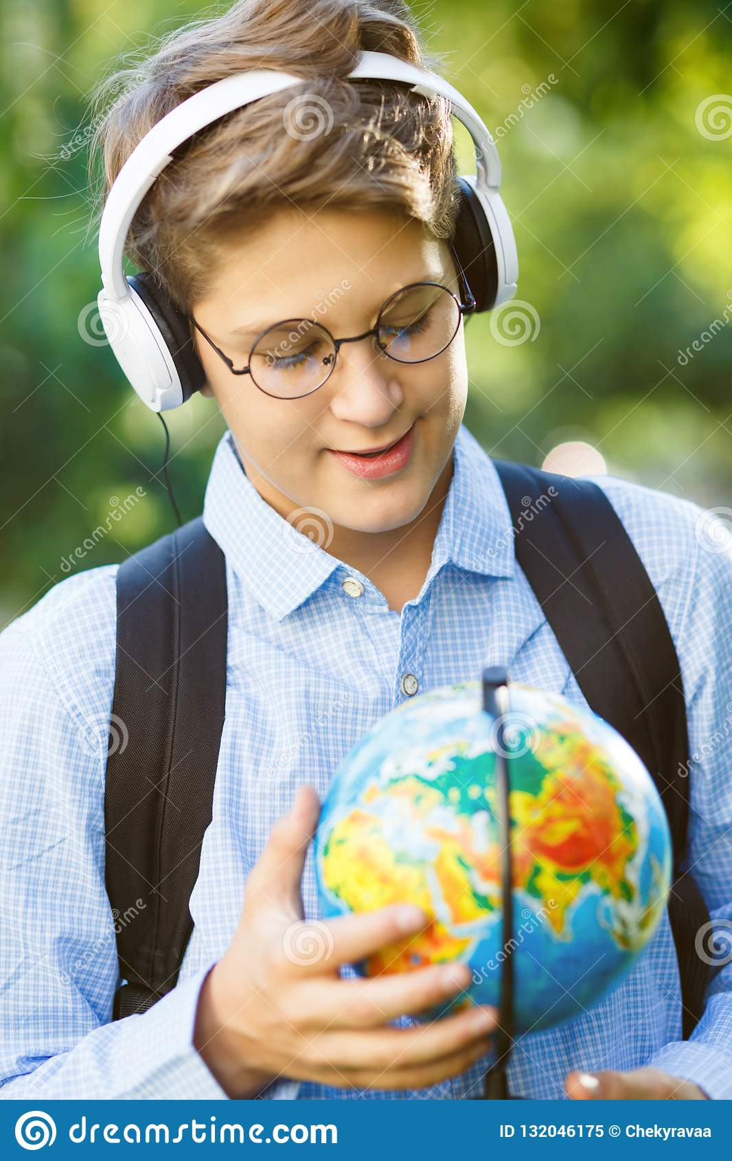 8768d2767e Cute young boy in round glasses and blue shirt stands on the grass and  holds a