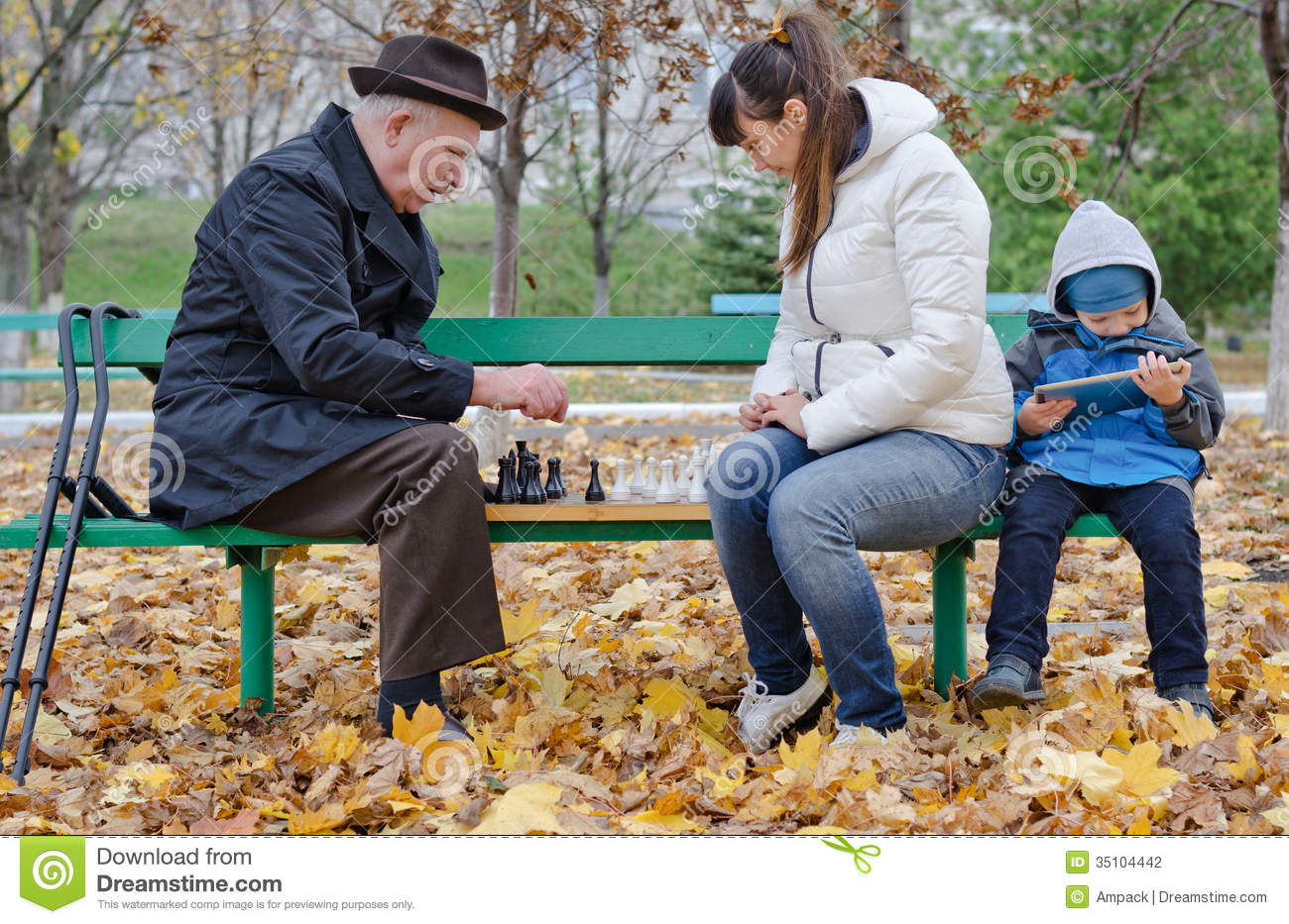 Cute Young Boy Sitting On A Park Bench Holding A Tablet ...