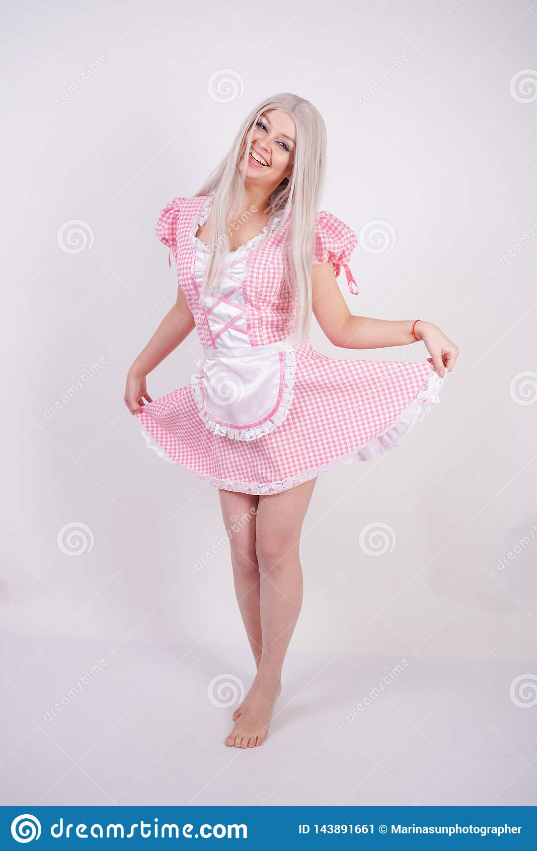 Cute young caucasian teen girl in pink plaid Bavarian dress with apron posing on white Studio solid background
