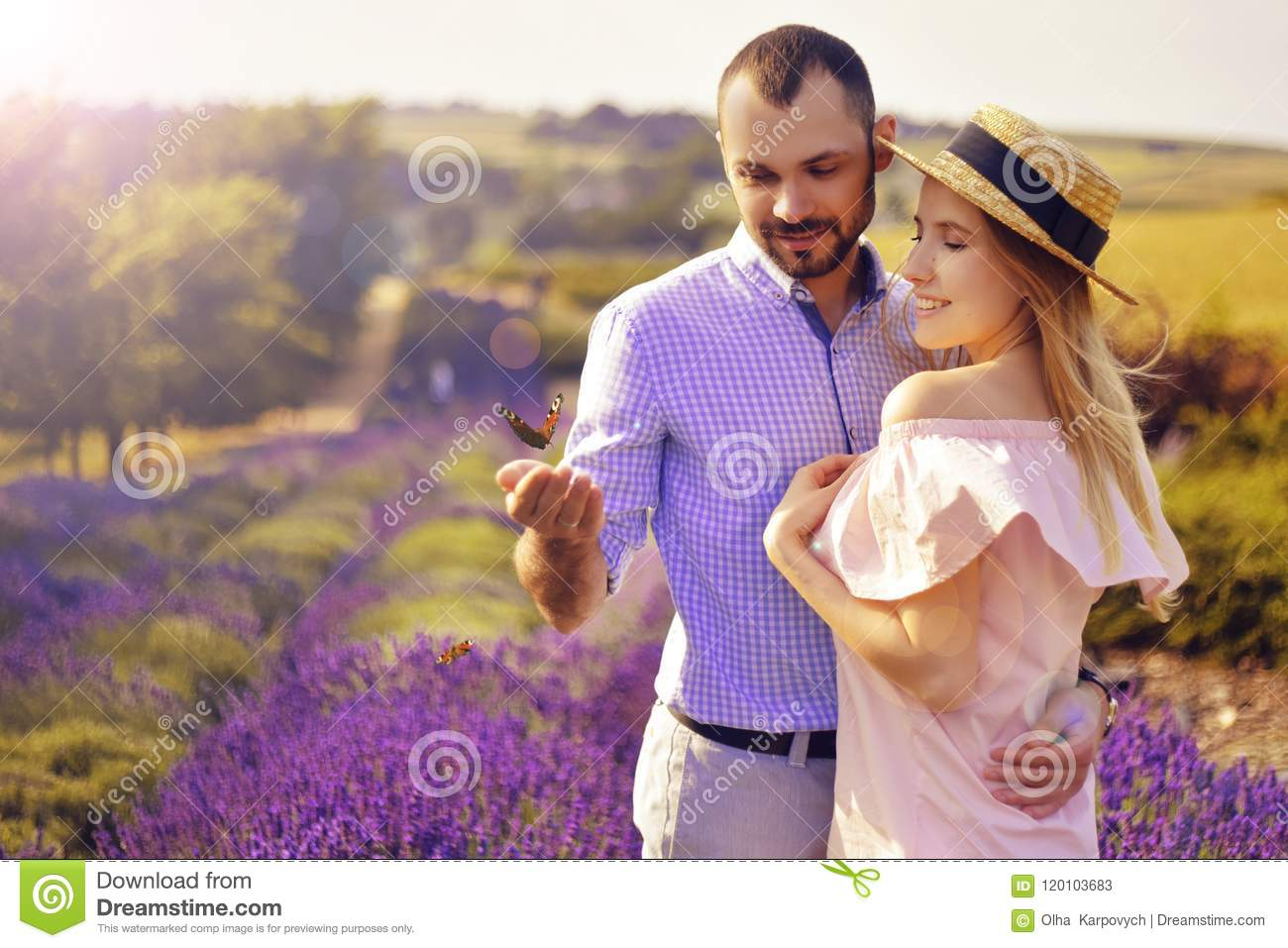 Cute young happy couple in love in a field of lavender flowers. Enjoy a moment of happiness and love in a lavender field.