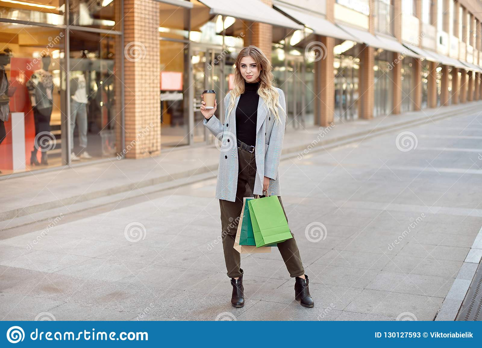 Cute young fashion woman with shopping bags standing near storefront shop windows on the street outdoors