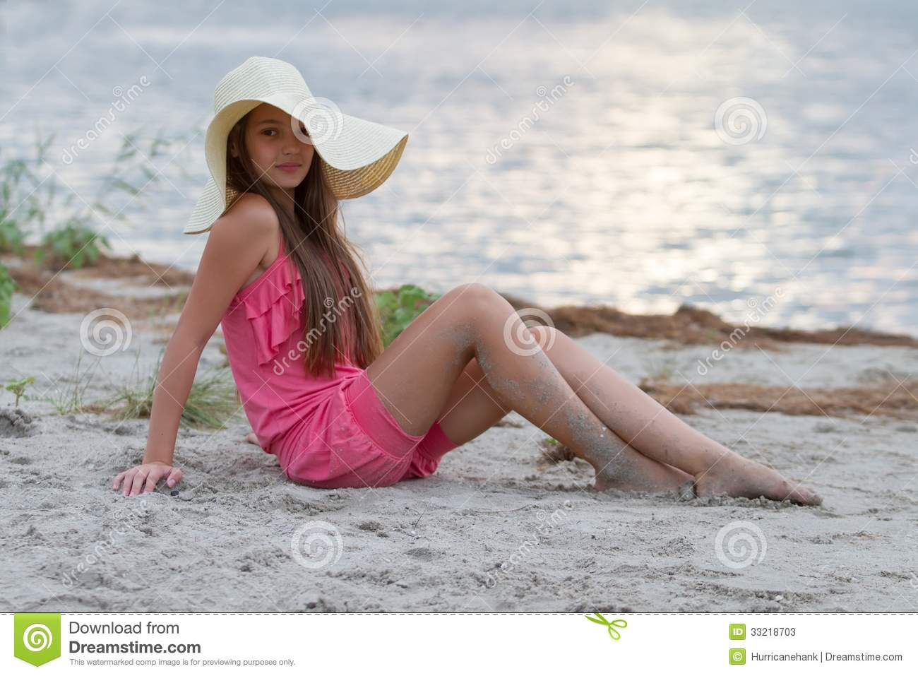 Cute Young Girl In Hat Sitting On The Beach Stock Image