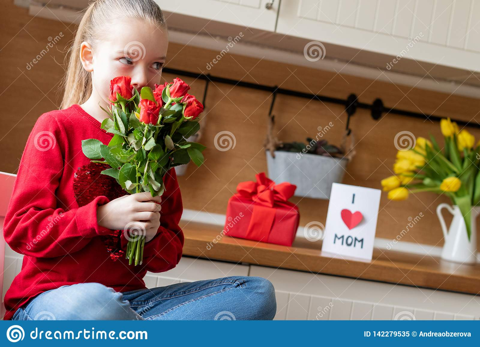 Cute young girl holding bouquet of red roses for her mom. Family celebration concept. Happy Mother`s Day or Birthday Background.