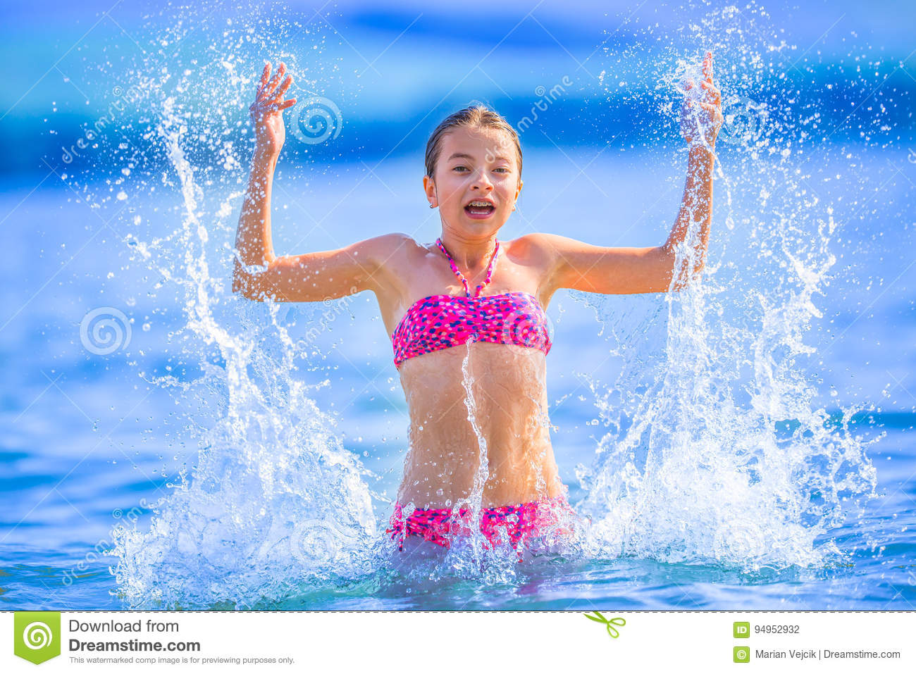Cute young girl playing in the sea. Happy pre-teen girl enjoys summer water and holidays in holiday destinations