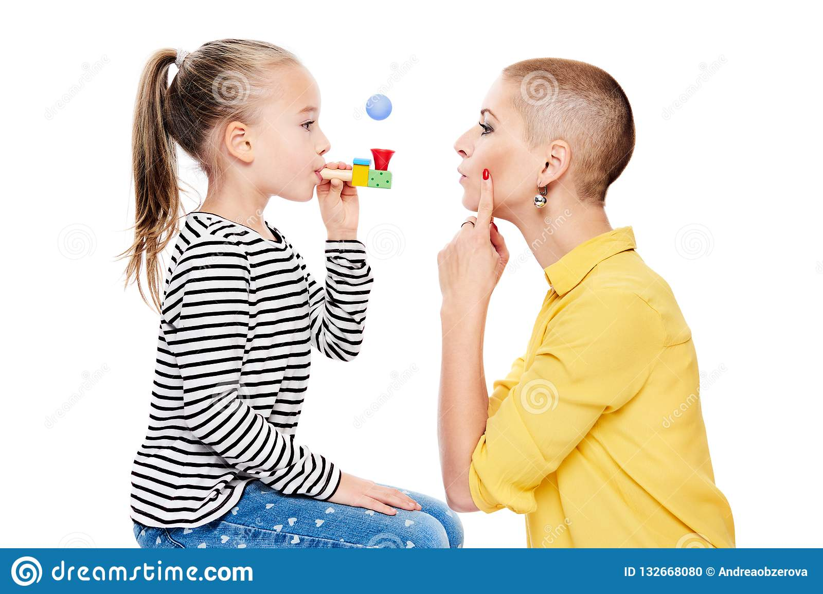 Cute young girl with speech therapist making special exercises at speech therapy office. Child speech therapy concept on white.