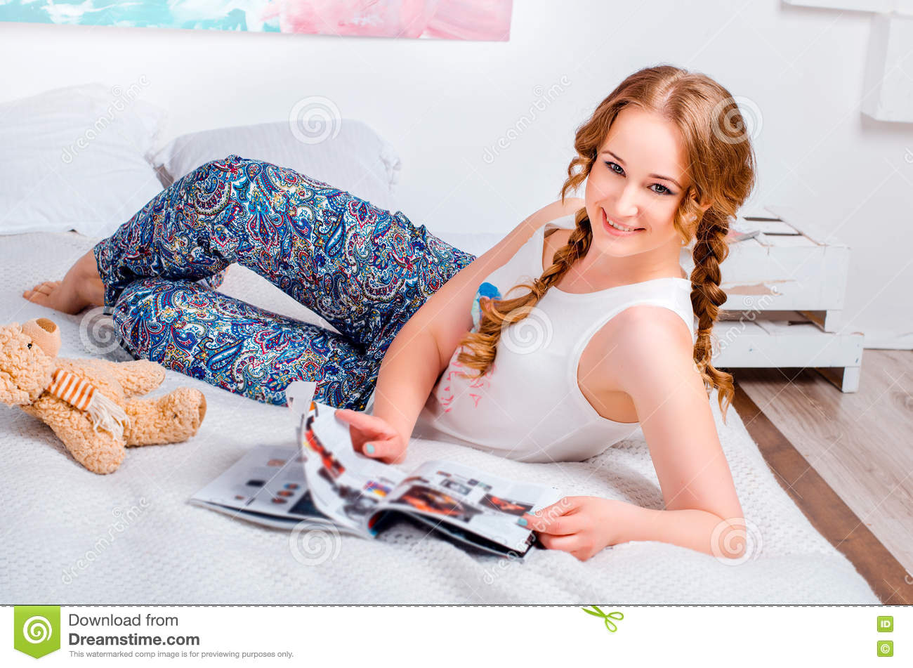 17921adad6f39e Cute young girl with two braids, at home wearing pajamas, lying on the bed,  with her soft toy bear, she reads a magazine and smiling