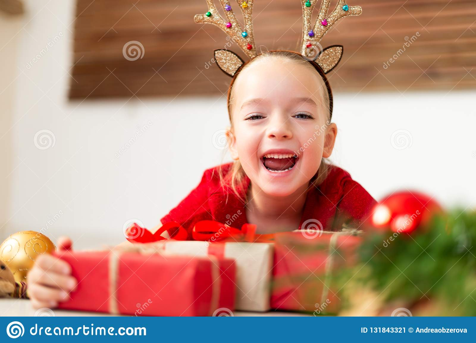 Cute young girl wearing costume reindeer antlers lying on the floor, surrounded by many christmas presents, screaming with joy.