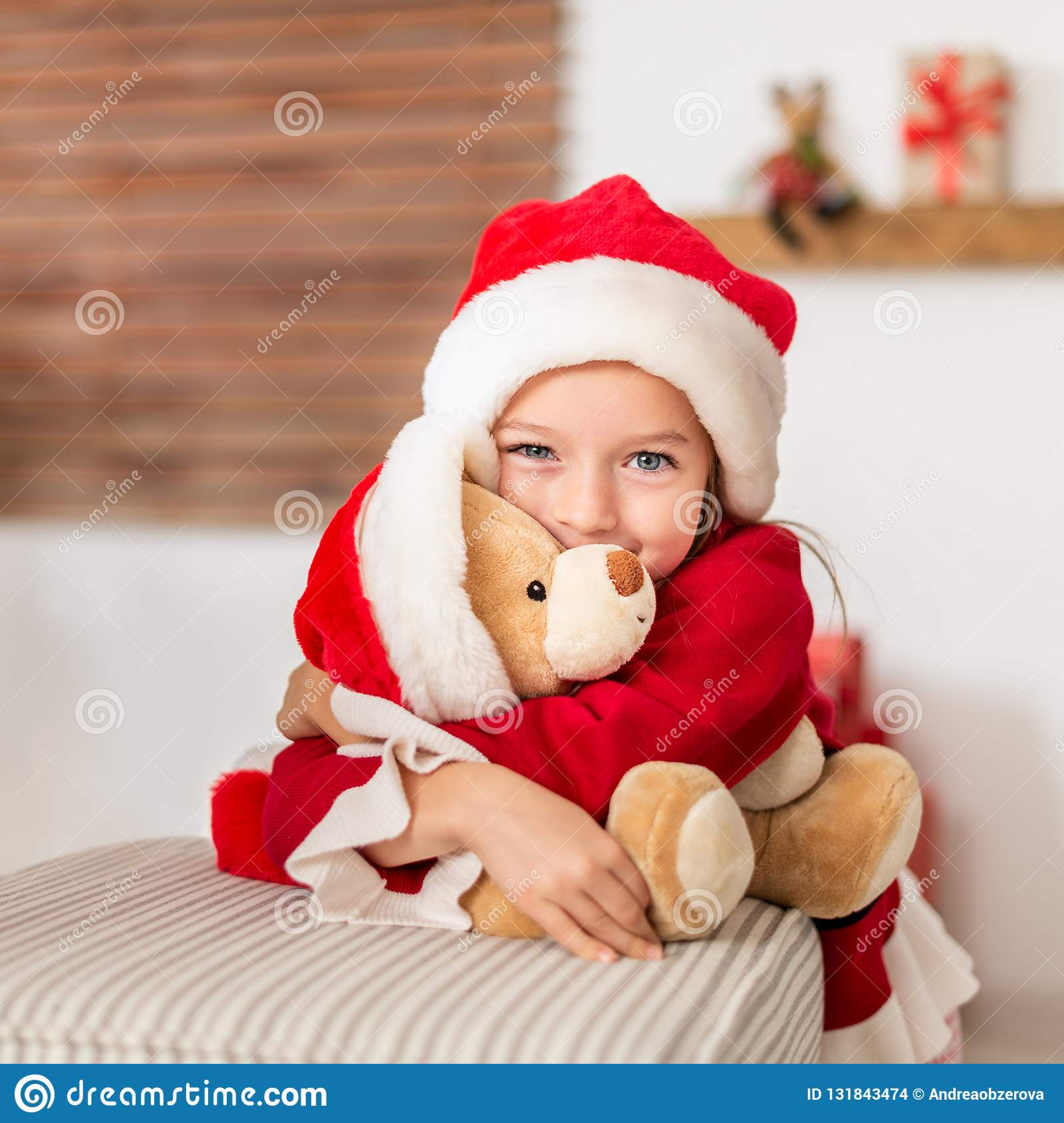 Cute young girl wearing santa hat hugging her christmas present, soft toy teddy bear. Happy kid with xmas present, smiling.