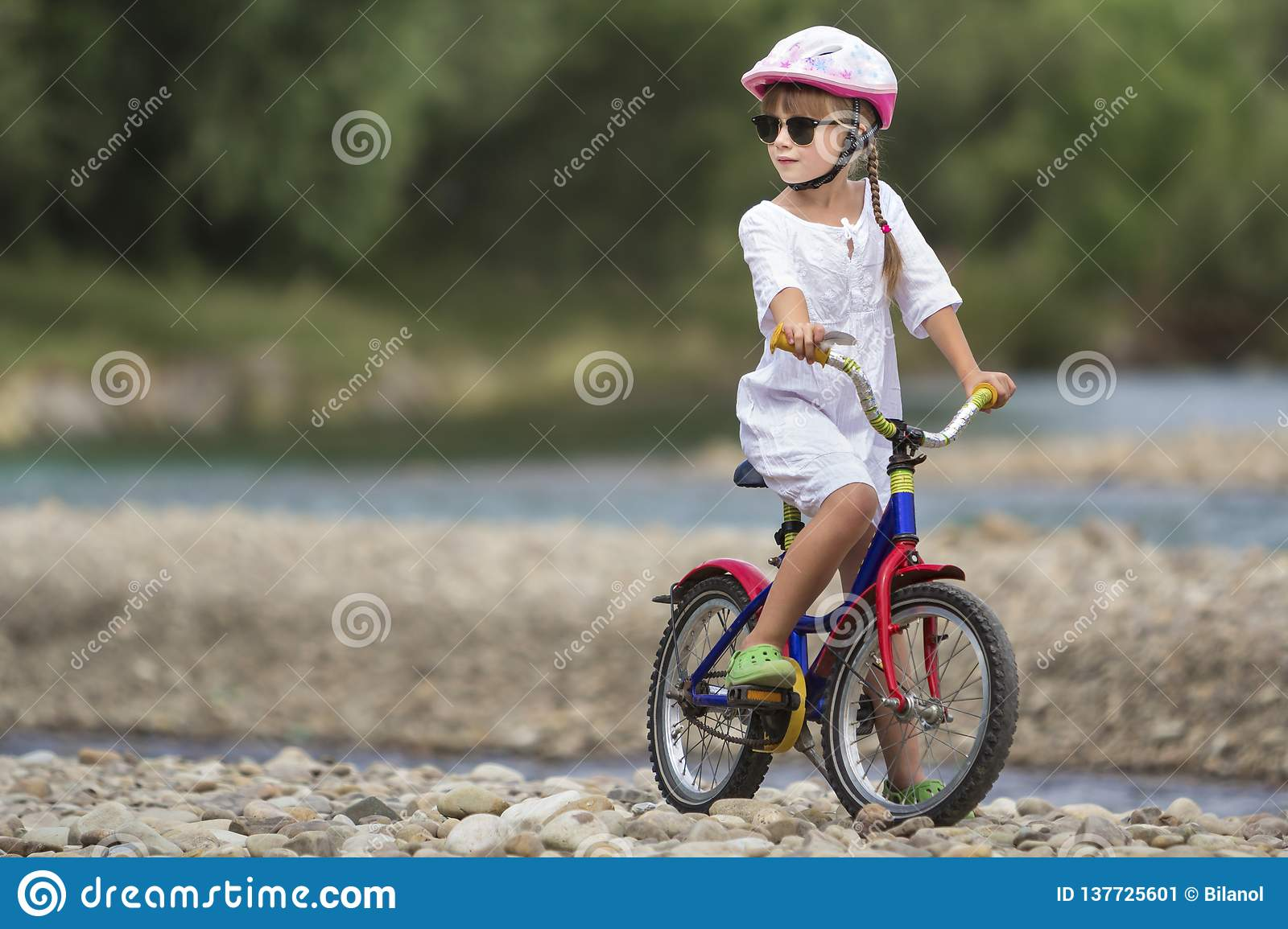 7b70b0b73bde Cute young girl in white clothing, sunglasses with long braids wearing pink  safety helmet riding child bicycle on pebbled river bank on blurred green  summer ...