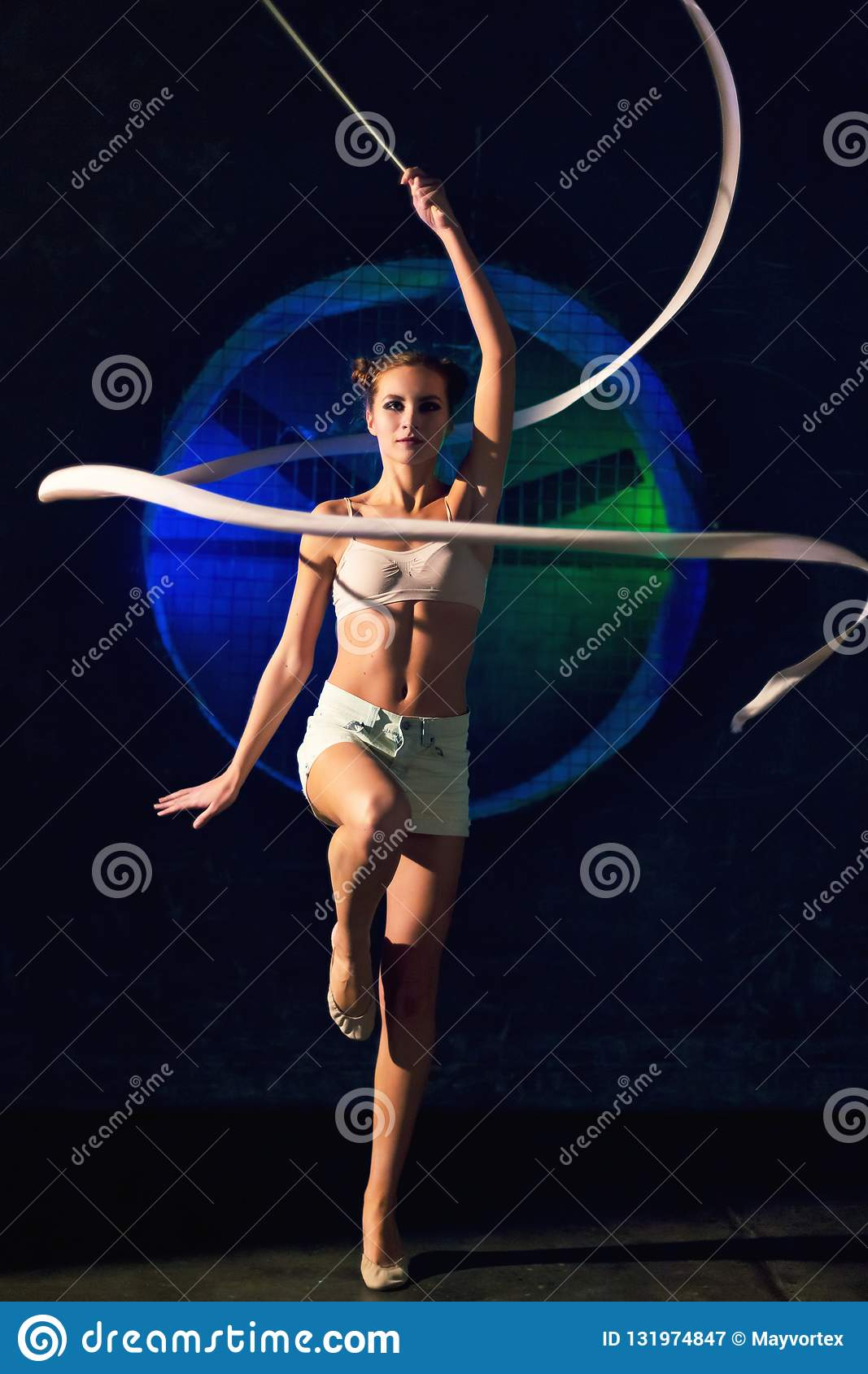 Cute young gymnast woman training with gymnastics tape on a dark background