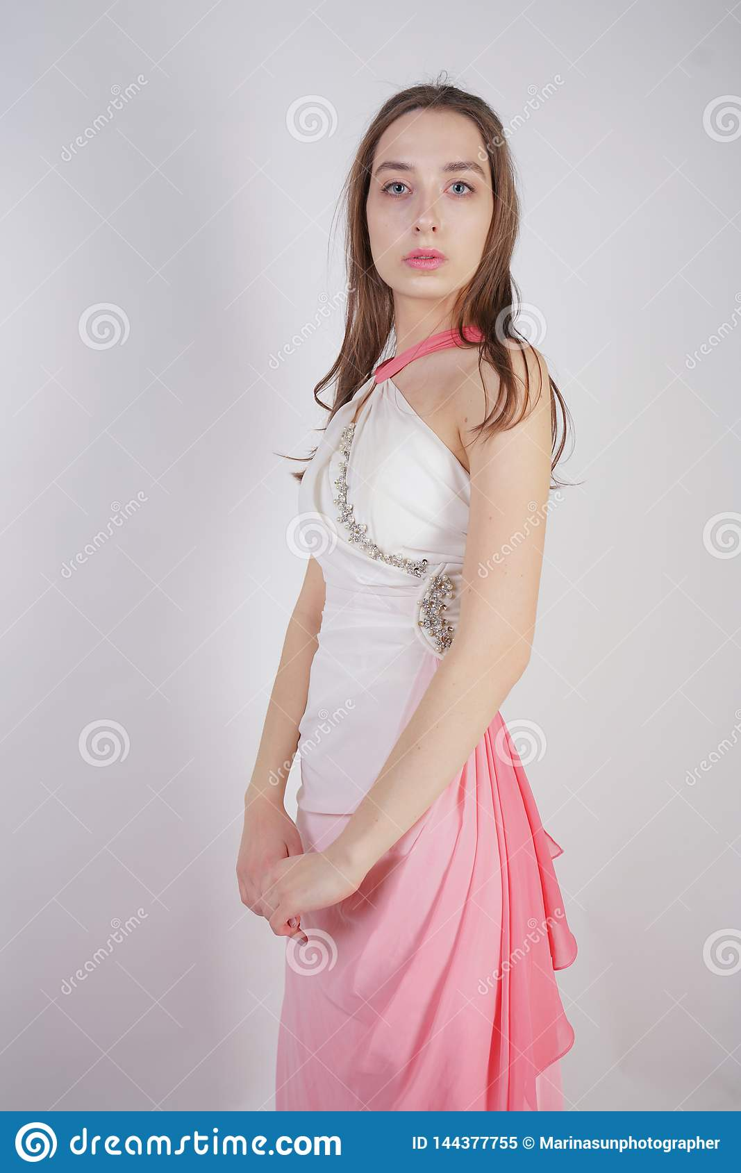 Cute young teen girl stands in summer dress with pink Ombre on white background in Studio.
