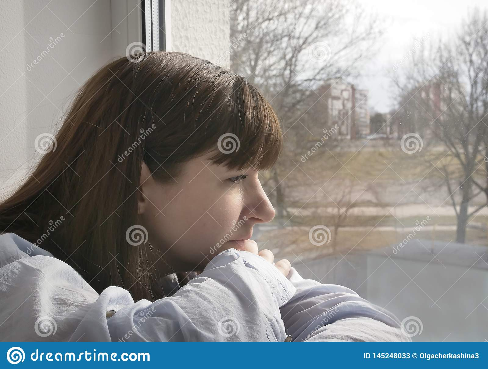 Cute young brunette woman sad looking window, close-up