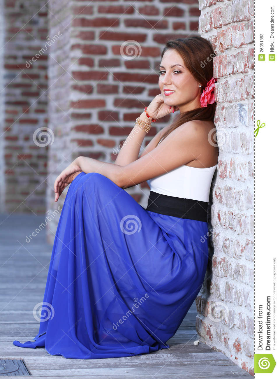 Cute young woman standing near a wall