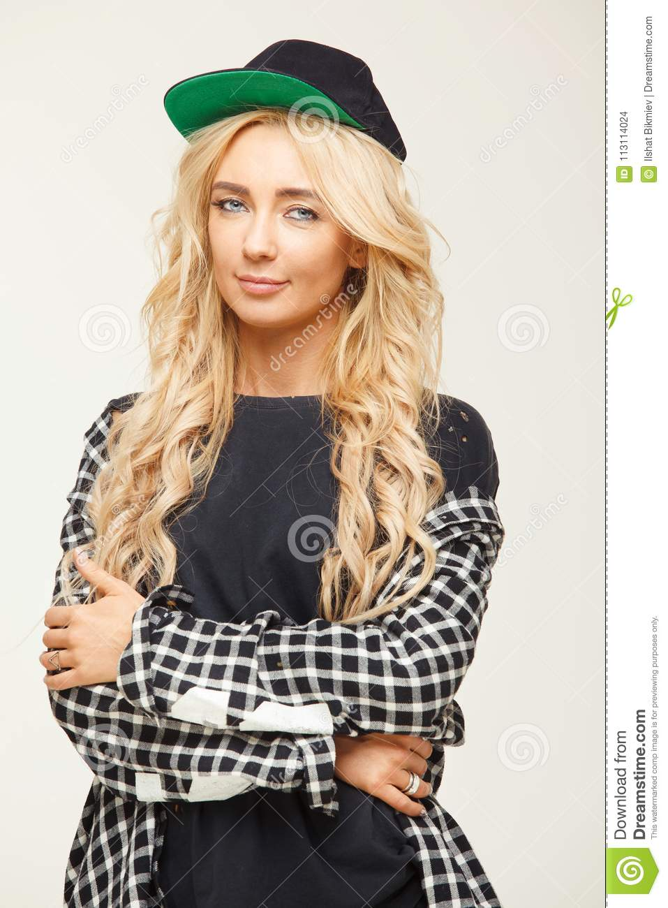 Cute young woman with voluminous blonde hair in baseball cap and shirt.  beautiful portrait of a stylish girl. 0486fd22d72