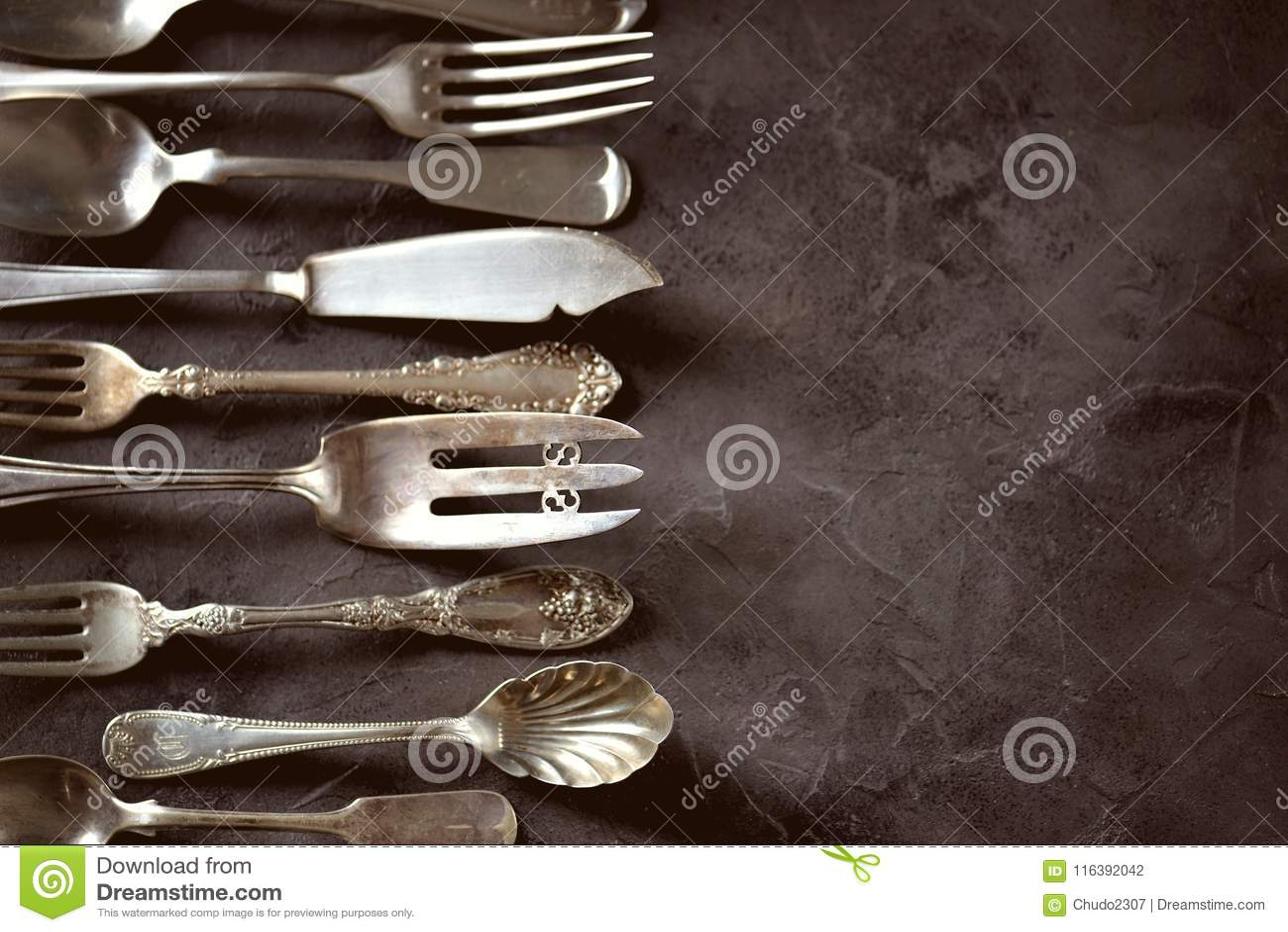 Cutelaria antiga do vintage - forquilhas, colheres, facas e outro em um fundo preto