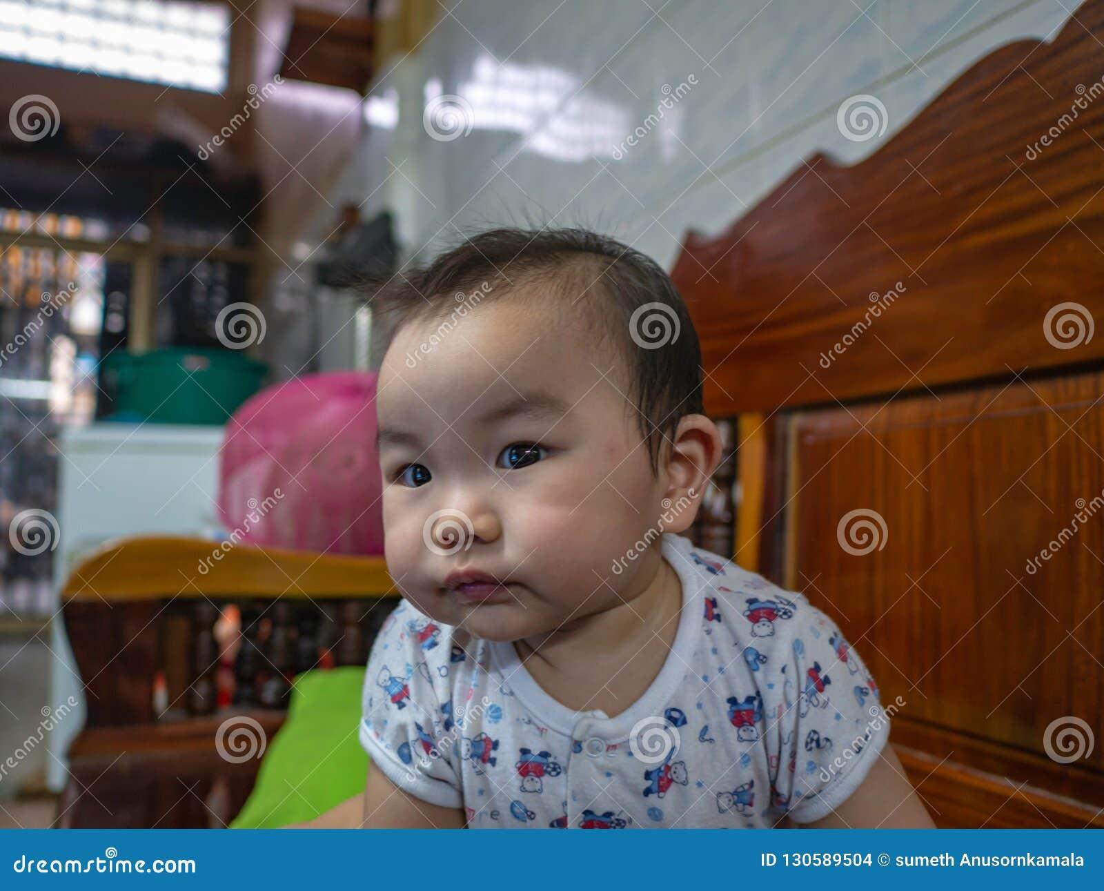 Cutie och den stiliga asiatiska pojken behandla som ett barn eller spädbarnet