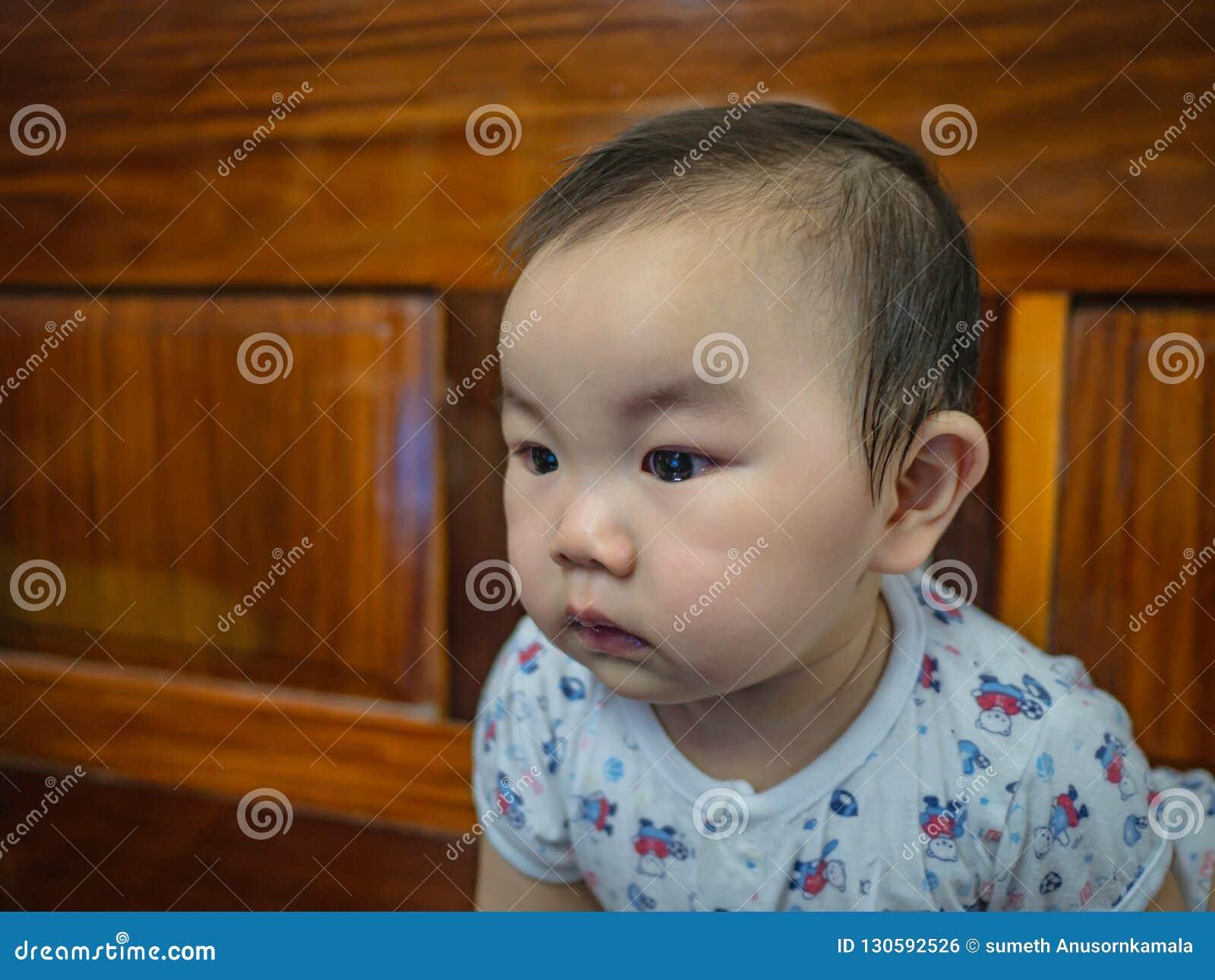 Cutie och den stiliga asiatiska pojken behandla som ett barn, eller spädbarnet gör en framsida som intresserat