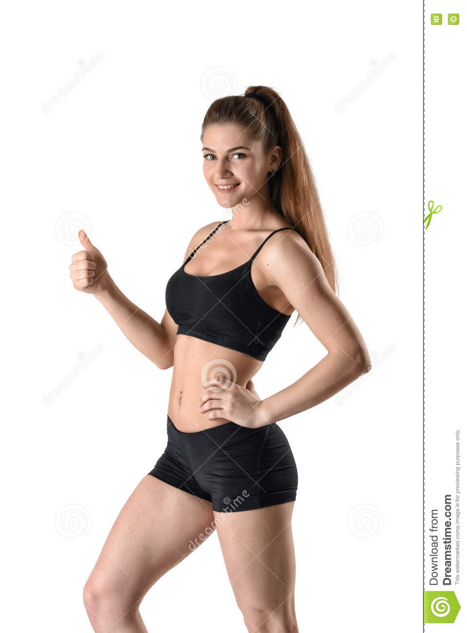 cf0d7f56d3ba2 Cutout young fitness girl in shorts and a tank top standing sideways and  showing thumbs up looking directly at the camera.